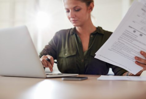 Young woman with documents working on laptop